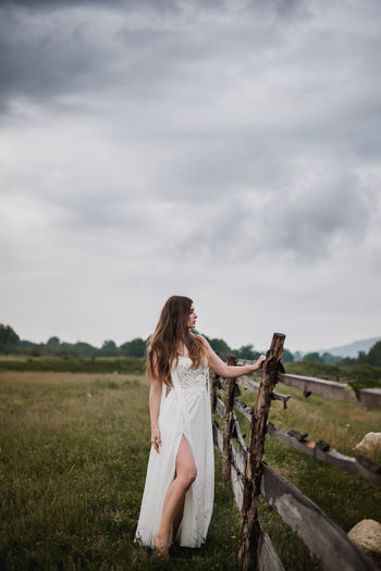 Wedding photography. A young bride in a beautiful white dress is standing near a wooden fence. Wedding in the style of the countryside. Photo taken in nature with daylight. Picturesque landscape. In the background a field with green grass, sky with clouds and mountains. Wedding Bride Cloud - Sky Countryside Day Dress Environment Fashion Field Grass Hair Hairstyle Land Landscape Long Hair Marriage  Nature One Person Outdoors Plant Sky Standing Wedding Dress Women Young Adult The Portraitist - 2018 EyeEm Awards The Still Life Photographer - 2018 EyeEm Awards The Fashion Photographer - 2018 EyeEm Awards 10 The Photojournalist - 2018 EyeEm Awards The Great Outdoors - 2018 EyeEm Awards The Traveler - 2018 EyeEm Awards The Creative - 2018 EyeEm Awards The Street Photographer - 2018 EyeEm Awards Love Is Love