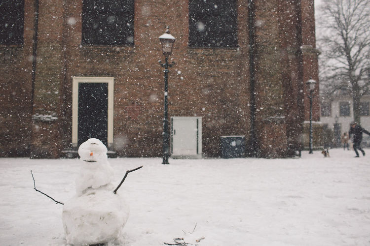 Snowman On Field Against Building