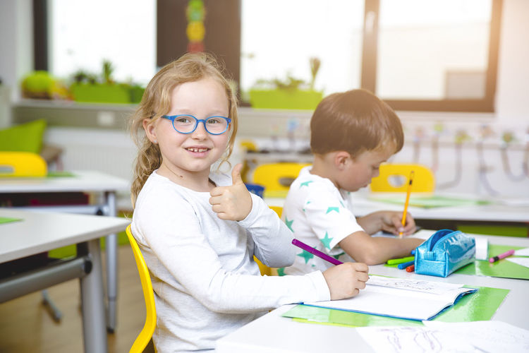 Portrait of girl showing thumbs up sign in classroom