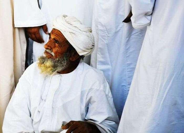 An older man calmly sitting outside of the bidding circle at Nizwa, Oman. OldmanNizwa Fort Oman_photo Oman Wisdom Market