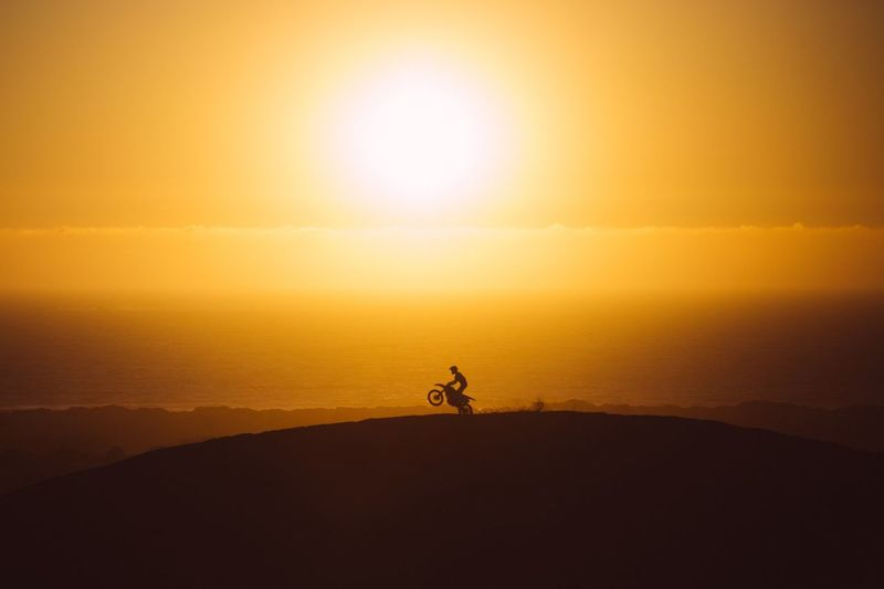Silhouette man riding motorcycle on mountain against orange sky