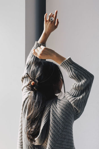 Close-up of woman standing against the wall