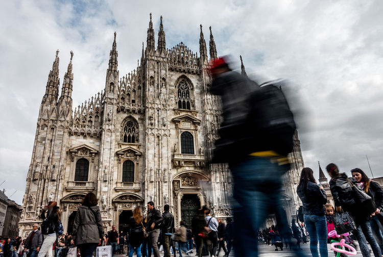 People In Front Of Milan Cathedral Against Cloudy Sky