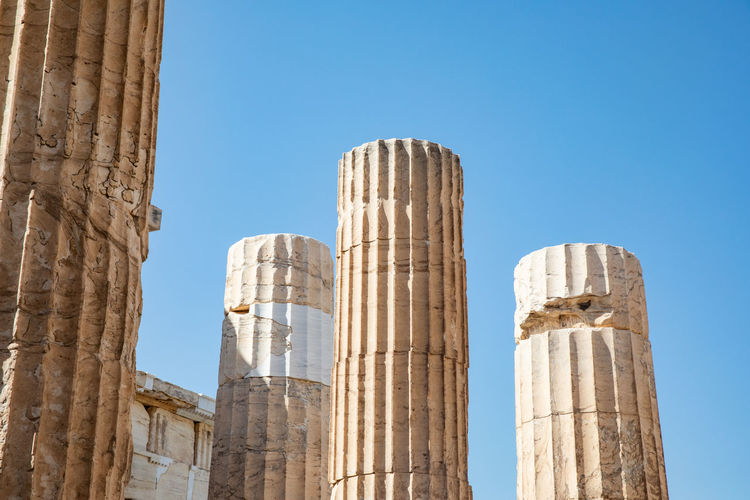 Low angle view of old columns against clear blue sky