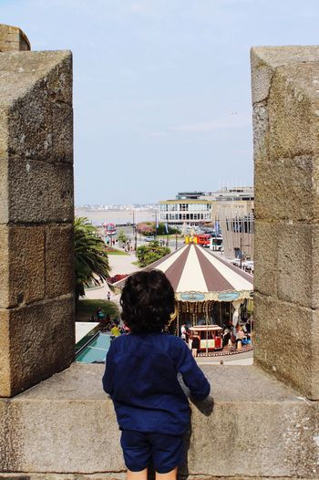 A child's dream Innocence Of Youth Innocence Contemplating Opening Wall Fortress Carousel Longing Envie Dreamy Curious Young Boy Rear View Architecture Real People Built Structure Sky Building Exterior One Person Childhood Child