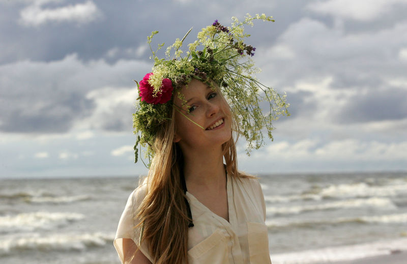 Portrait of beautiful woman standing by sea against sky