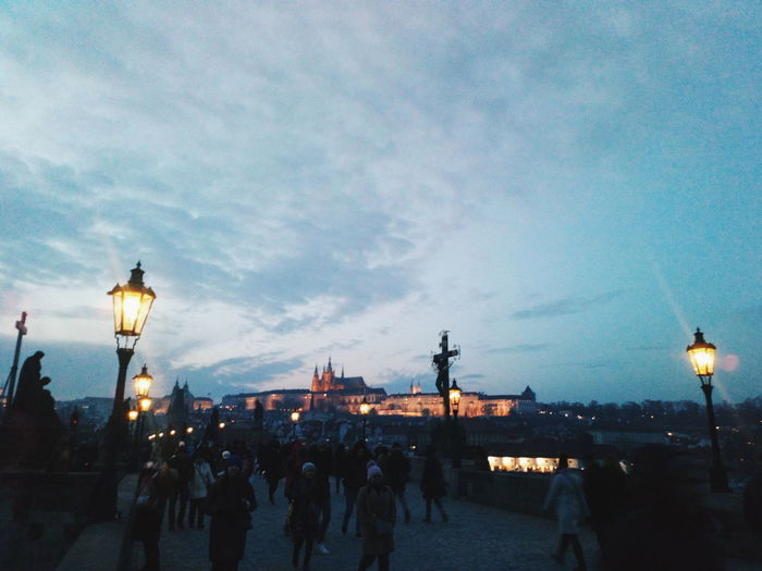 People walking on illuminated street against sky in city
