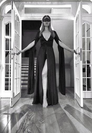 Full length of sensuous woman wearing eye mask standing at doorway in house