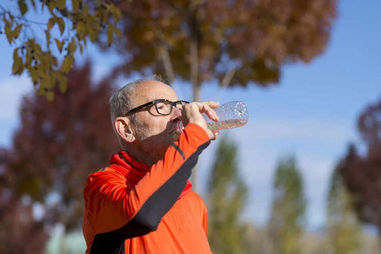 Handsome senior jogging man drinking fresh water from bottle after morning run Running Close-up Day Drink Exercising Eyeglasses  Focus On Foreground Healthy Lifestyle Holding Jogging Leisure Activity Lifestyles Mature Adult Mid Adult Nature One Person Outdoors People Real People Sky Smiling Sport Sunlight Tree Water