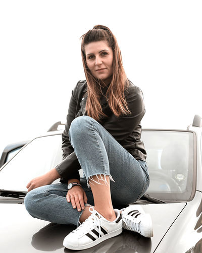 Portrait of young woman sitting on car