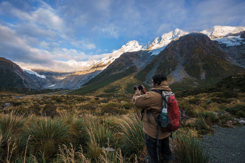 Side view of backpacker photographing field by mountains against sky