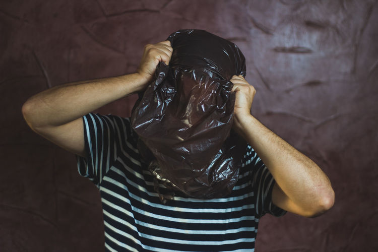 Man With Face Covered By Plastic Bag Against Wall