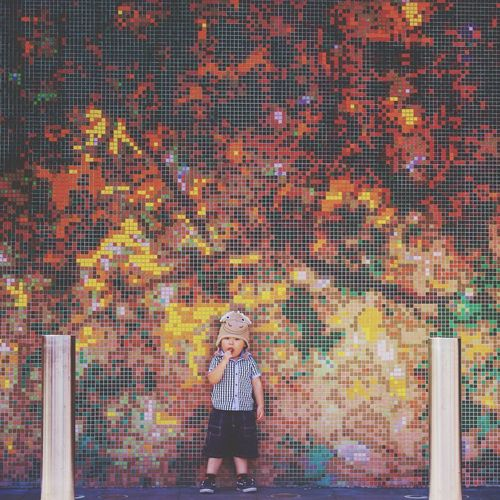 Cute boy standing against mosaic wall
