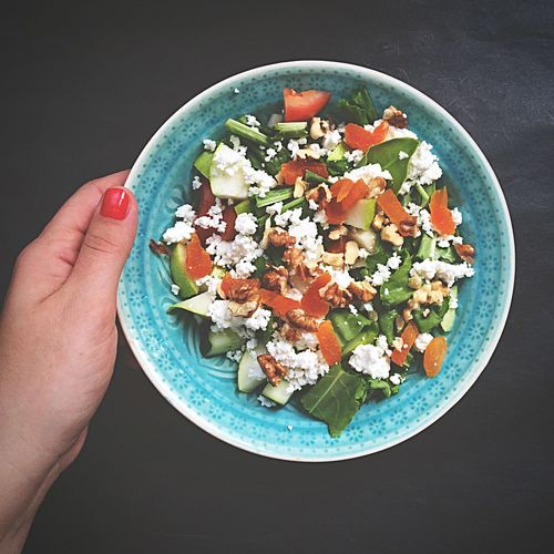Cropped hand holding salad on plate