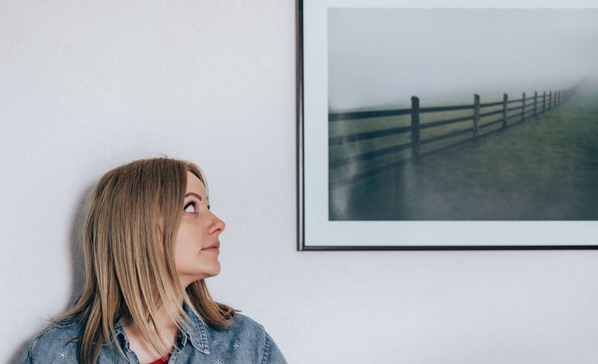 Woman Looking At Frame Against Wall