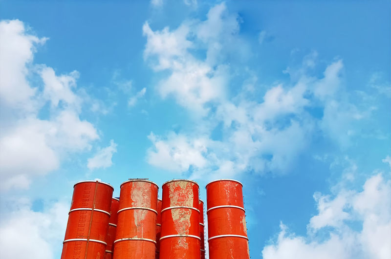Low angle view of mixed concrete tanks against blue cloudy sky