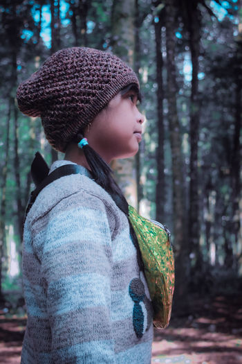 Side view of woman wearing hat in forest