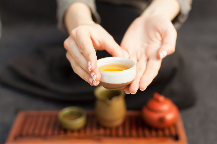 Midsection of woman holding tea while sitting on floor