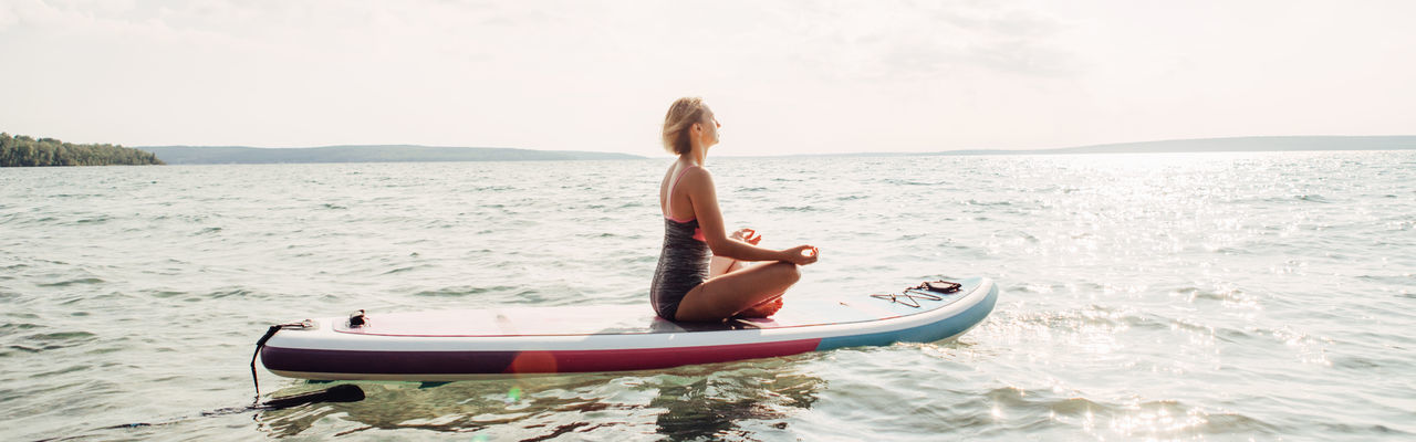 Woman on paddleboard in sea against sky