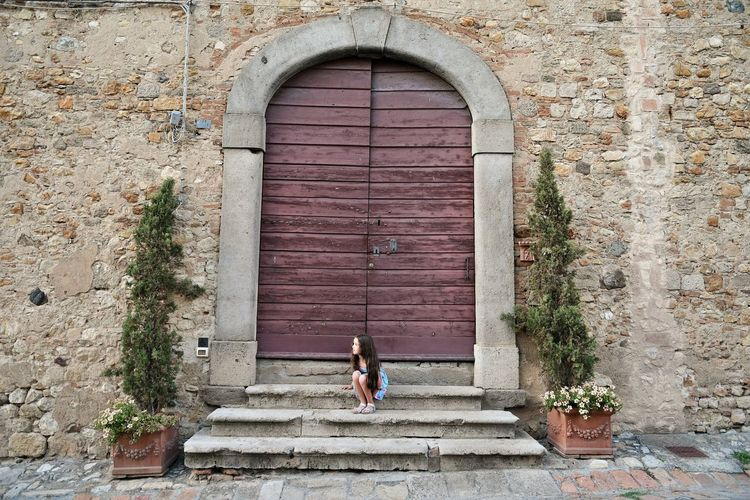 Cute girl sitting on steps outside closed old building door
