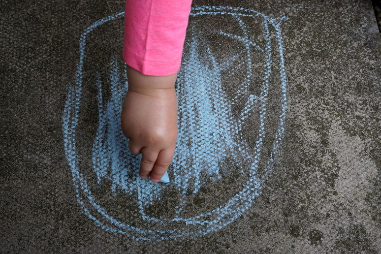 Close-up of girl drawing on concrete