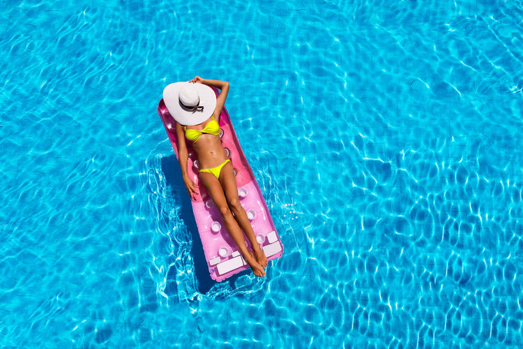 Attractive girl is relaxing on a floating mattress in a pool Float Hat Hot Relaxing Swimming Tanning Vacations Woman Attractive Bikini Blue Day Floating On Water Girl Inflatable  Mattress Outdoors Sexygirl Sleeping Summer Sunhat Suntanning Swimming Pool Water Yellow
