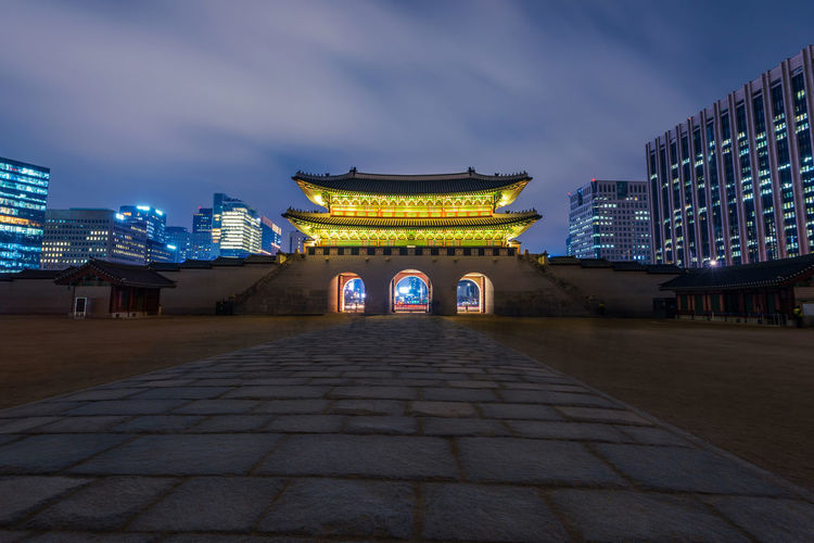 Illuminated Gate And Buildings Against Cloudy Sky At Night