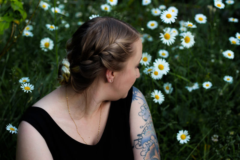Portrait of young woman sitting in  a field of daisies
