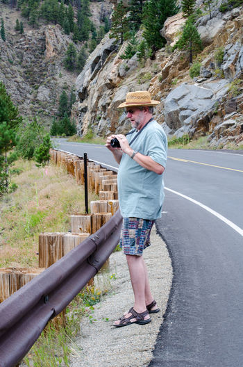 Full Length Of Senior Man Photographing While Standing On Roadside Against Mountains