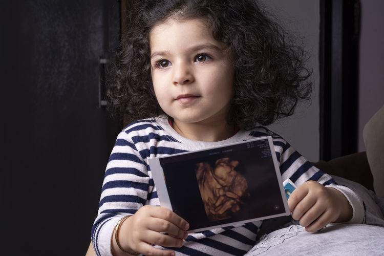 Cute girl holding ultrasound photograph at home