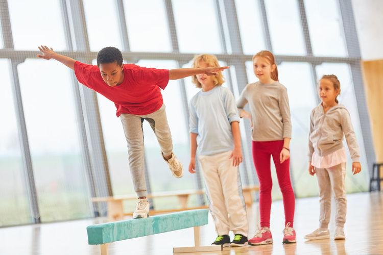 Students looking at boy balancing on beam in school gymnasium