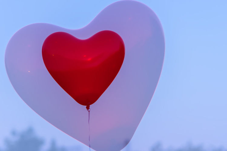 Close-up of heart shape balloons against blue sky