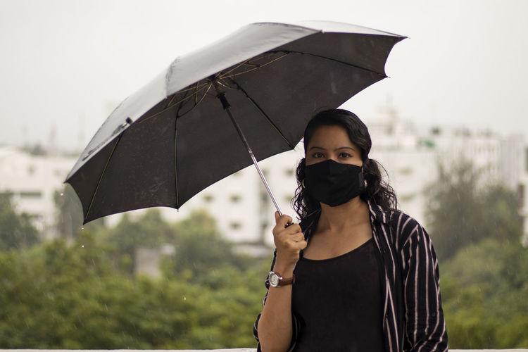 Portrait of man holding umbrella standing during rainy season