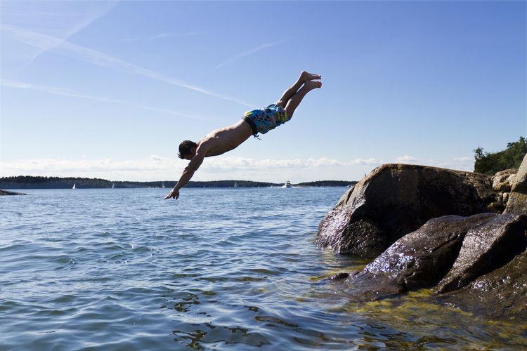 Man surfing on rock in sea against sky