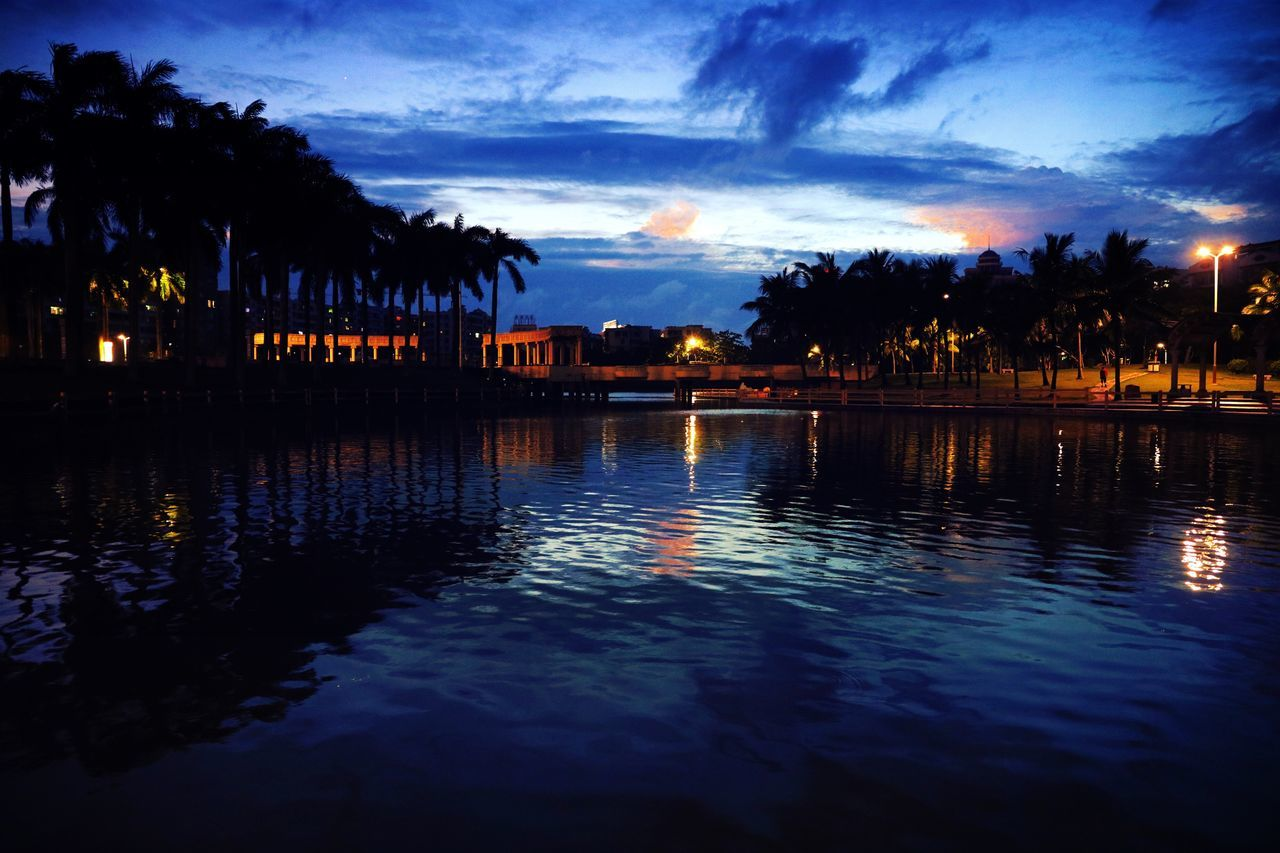 reflection, water, silhouette, cloud - sky, sky, sunset, dusk, waterfront, outdoors, tranquility, tranquil scene, beauty in nature, no people, nature, scenics, tree, built structure, building exterior, architecture, illuminated, day