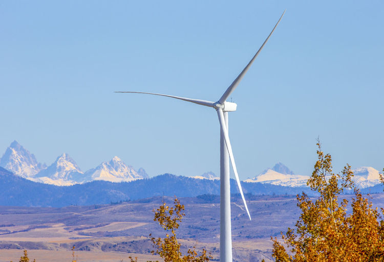 Wind turbines on snowcapped mountains against blue sky