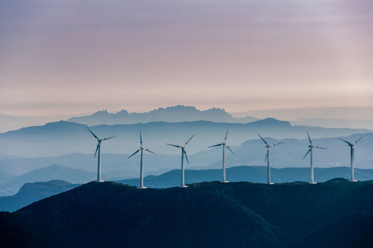 Wind turbines on mountain against sky during sunset