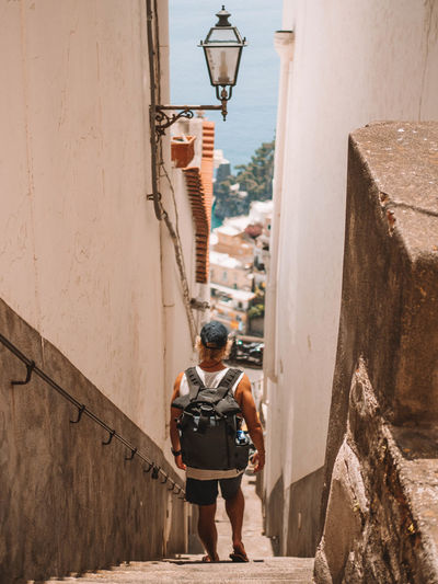 Rear view of man with backpack walking down alley amidst buildings