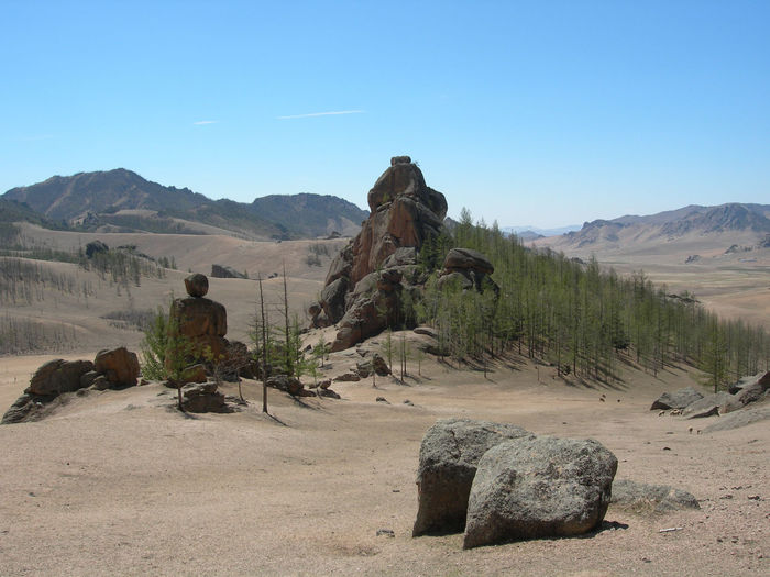 Rock Formations At Arid Landscape Against Blue Sky On Sunny Day