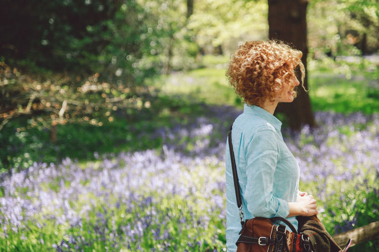 Side view of woman walking by plants at forest on sunny day