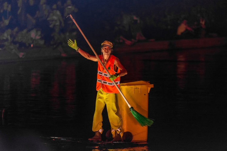 Full length of man standing by lake at night