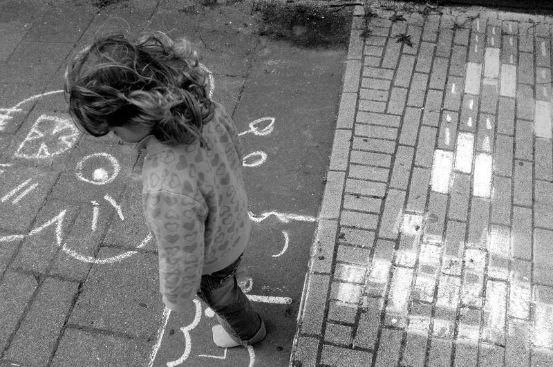 High Angle View Of Girl Standing On Footpath
