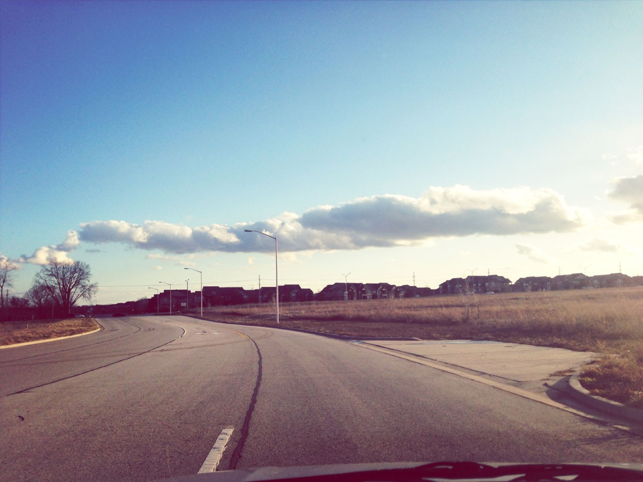 transportation, the way forward, road, diminishing perspective, road marking, sky, vanishing point, country road, landscape, empty, blue, long, empty road, asphalt, cloud - sky, cloud, street, highway, outdoors, tranquil scene