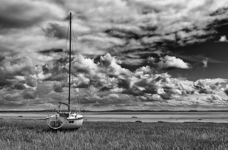 Sailboat moored on grassy field against cloudy sky