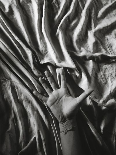 Close-Up Of Hand On Crumbled Bedsheet