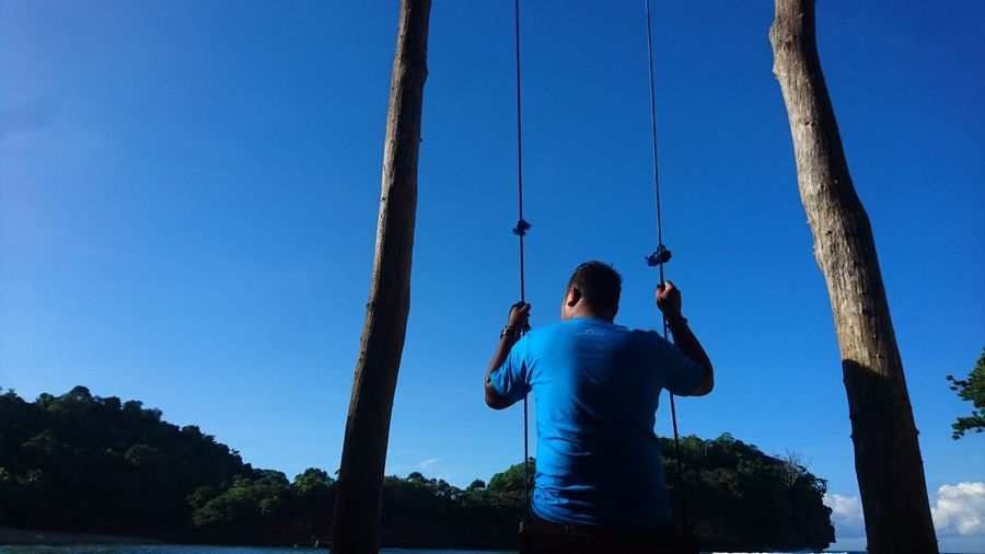 Low angle rear view of young man swinging against blue sky during sunny day
