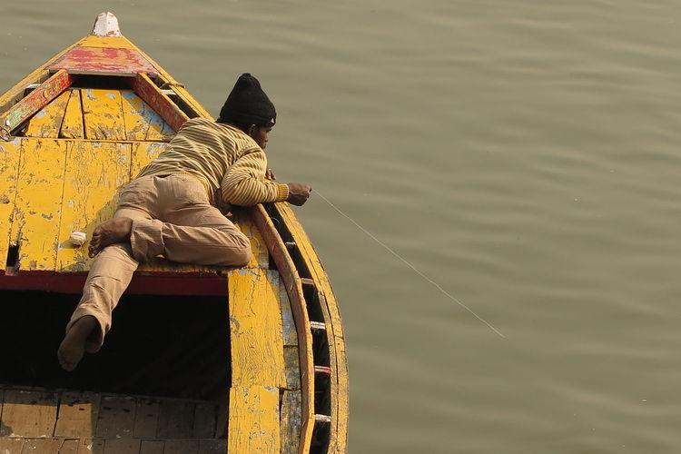 Man fishing while lying on boat at lake