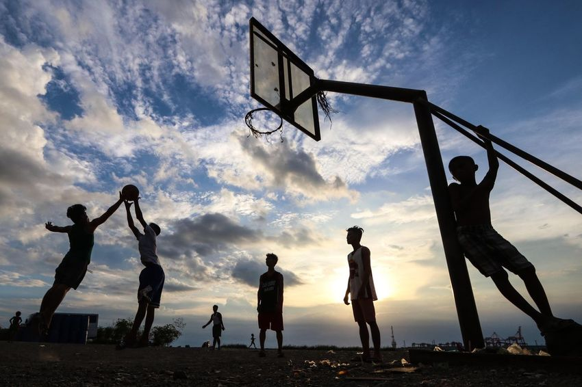 Filipino men are silhouetted against a sunset as they play basketball in a makeshift court in Baseco Compound in Tondo, Manila on Tuesday afternoon, June 6. Basketball is the most popular sport in the Philippines, played on both the amateur and professional levels. Basketball - Sport Basketball Hoop Sport Sunset Low Angle View Dusk Human Interest Street Photography Layers