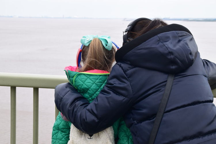 Rear view of mother and daughter in warm clothing looking at view