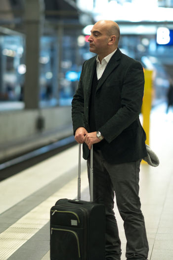 Man with luggage standing on railroad station platform